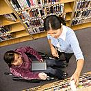 Asian woman helping woman in wheelchair at library