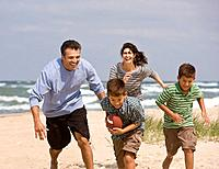 Hispanic family playing football on beach