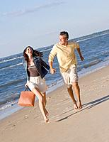 Hispanic couple running on beach