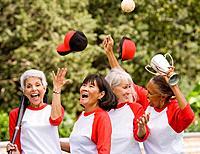 Multi_ethnic senior women in baseball uniforms cheering