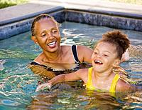 African grandmother helping granddaughter to swim