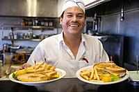 Hispanic male cook holding plates of food (thumbnail)