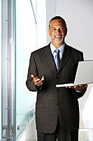African businessman holding laptop