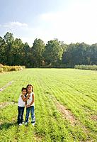 Hispanic sisters hugging in field