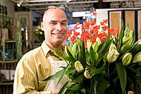 Hispanic male florist arranging flowers