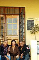 African mother and adult sons on porch steps