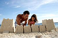 Hispanic father and daughter building sand castle