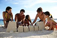Hispanic family building sand castle