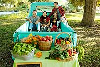 Multi_ethnic family in truck at farm stand