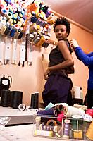 African woman trying on dress at seamstress shop