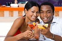 Multi_ethnic couple toasting with cocktails