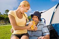 Hispanic woman feeding sandwich to boyfriend