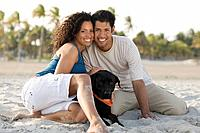 Hispanic couple and dog on beach