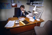 Business Man Sitting At Desk Using Telephone