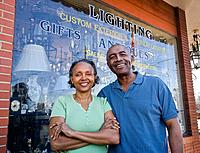 Senior African couple in front of business