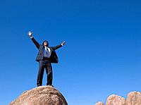 African businessman standing on top of rock