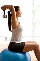 Hispanic woman exercising with weights (thumbnail)