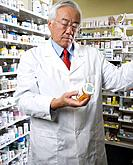 Senior Asian pharmacist reading medication