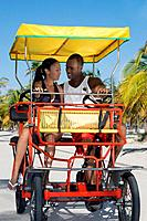 Multi_ethnic couple riding in pedal cart