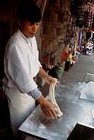 Chinese man preparing noodles in a street market in Shanghai China
