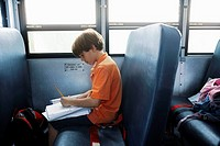 Little Boy Doing Schoolwork on a School Bus