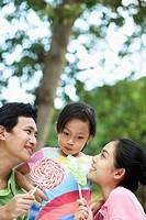 Parents Offering Lollipops to Daughter