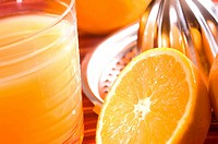Close_up of a juicer with an orange slice and a glass of orange juice
