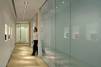 BAKER BOTTS, 41 LOTHBURY, LONDON, EC2 MOORGATE, UK, GENSLER, INTERIOR, LANDSCAPE VIEW OF CORRIDOR WITH FIGURE AND MEETING ROOM TO RIGHT