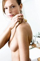 Portrait of a naked young woman massaging her shoulders with a wooden massager
