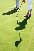 Golfers on green, shadow, high angle view
