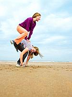 Two females playing leap_frog on beach