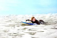 Female lying on surfboard, paddling