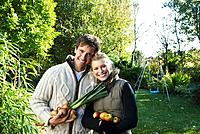 Happy couple holding vegetables