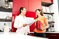 Couple discuss paperwork in kitchen