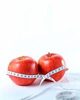 Two apples with measuring tape