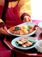 Korean woman serving seafood dish