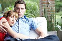 Couple outdoors on patio lounger where the woman is sleeping (thumbnail)