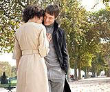 Couple standing outdoors in park being affectionate and smiling