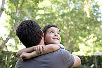 Man outdoors hugging smiling young boy