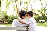 Man outdoors sitting on bench with young boy being affectionate toward him and smiling