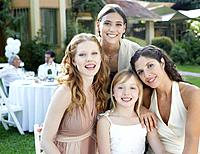 Three women and young girl at an outdoor party smiling