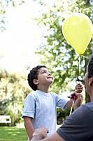 Man outdoors giving smiling young boy a balloon