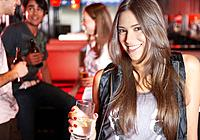Woman holding beverage in nightclub smiling