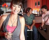 Woman with beverage standing by pool tables smiling