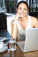 Woman in restaurant with laptop smiling