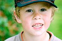Blond, good looking child posing in a farm with a beisbol hat in Cambidge, New Zealand