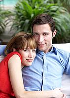 Couple relaxing in living room smiling (thumbnail)
