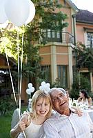 Senior man at outdoor party with young girl holding balloons and smiling