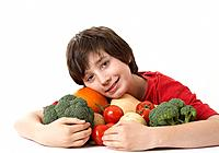 Boy hugging a pile of assorted vegetables smiling