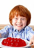 Young boy in kitchen holding a plate of jello smiling